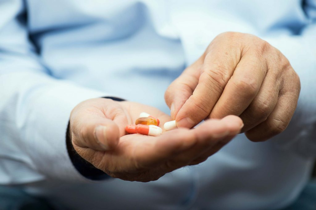 man with pills in hand