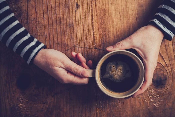 hands holding a mug of black coffee