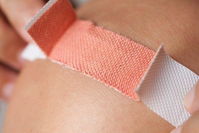 applying a band-aid to a cut