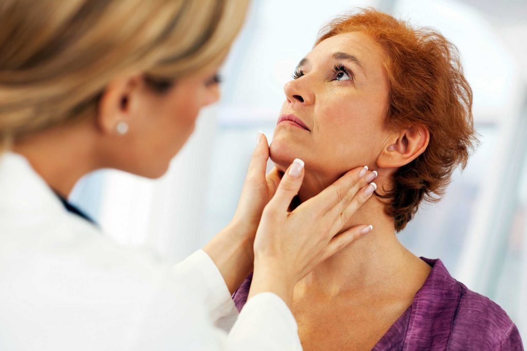 Female doctor checking a woman's neck lymph nodes