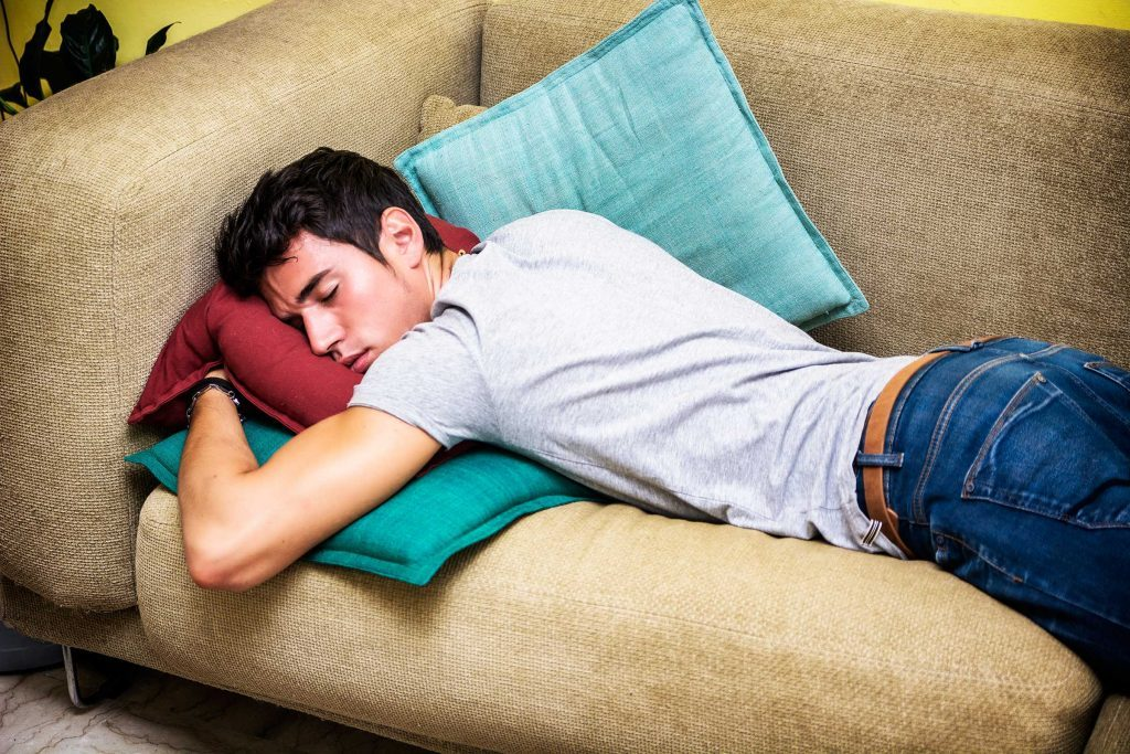 man sleeping face-down on couch