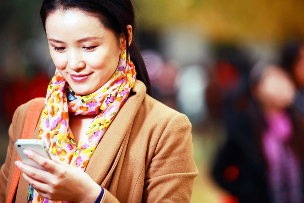 smiling woman look at phone in her hand
