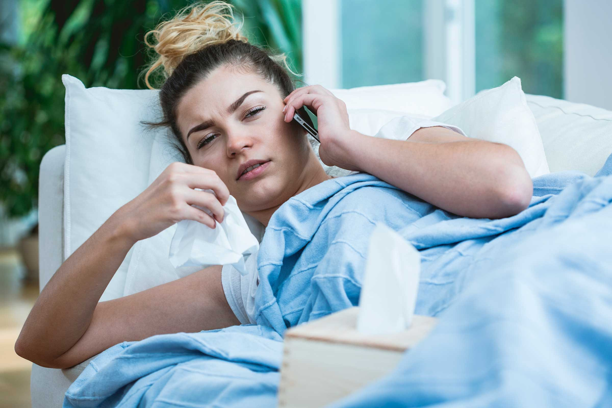 Sick woman in bed, talking on her phone and holding a tissue.