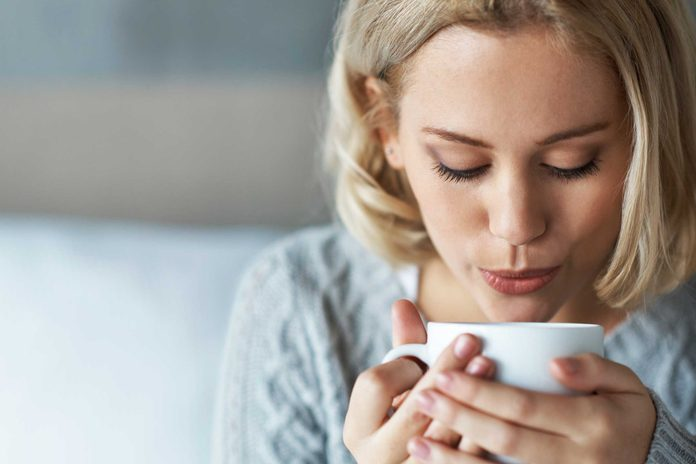 woman blowing on a cup of coffee