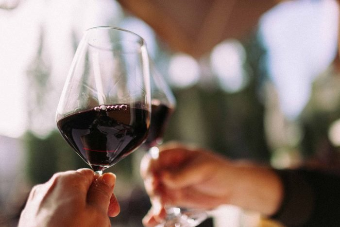 two hand holding wine glasses with red wine, clinking glasses