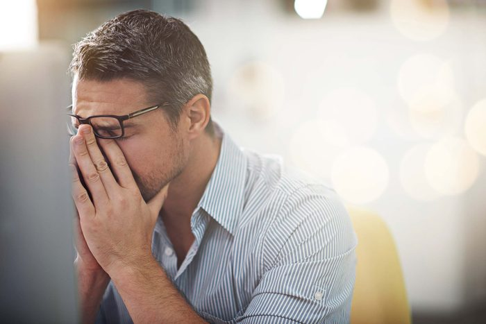 man in pain pressing his fingers against the bridge of his nose