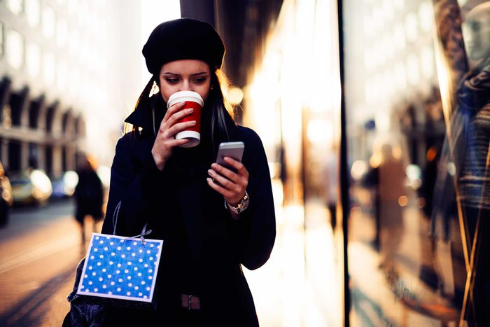 woman drinking coffee while shopping