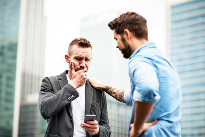 worried man looking at phone, another man with hand on his shoulder
