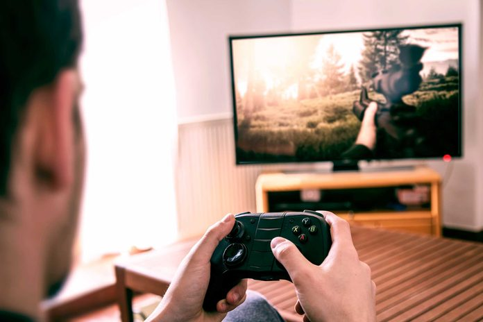 man playing a video game with controller in hand
