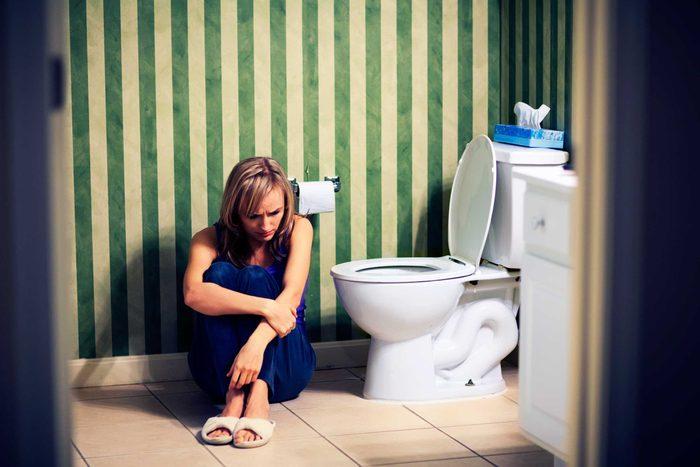 sad woman sitting next to toilet