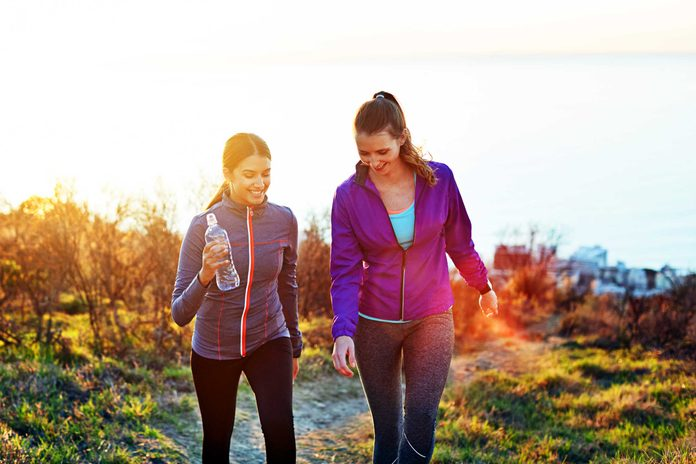 two women hiking up hill at sunset