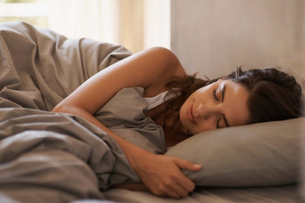 woman on her side in bed sleeping peacefully