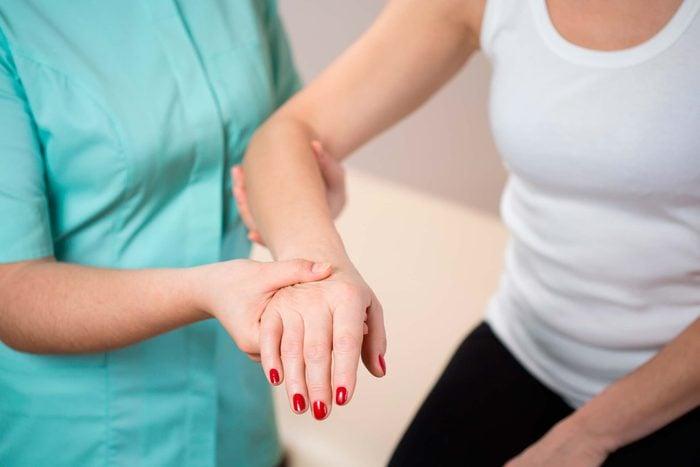 nurse checking a woman's right arm