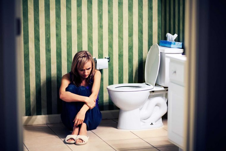 constipated woman slumped near toilet