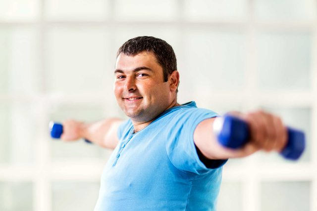 heavy man lifting dumbbells out to his sides