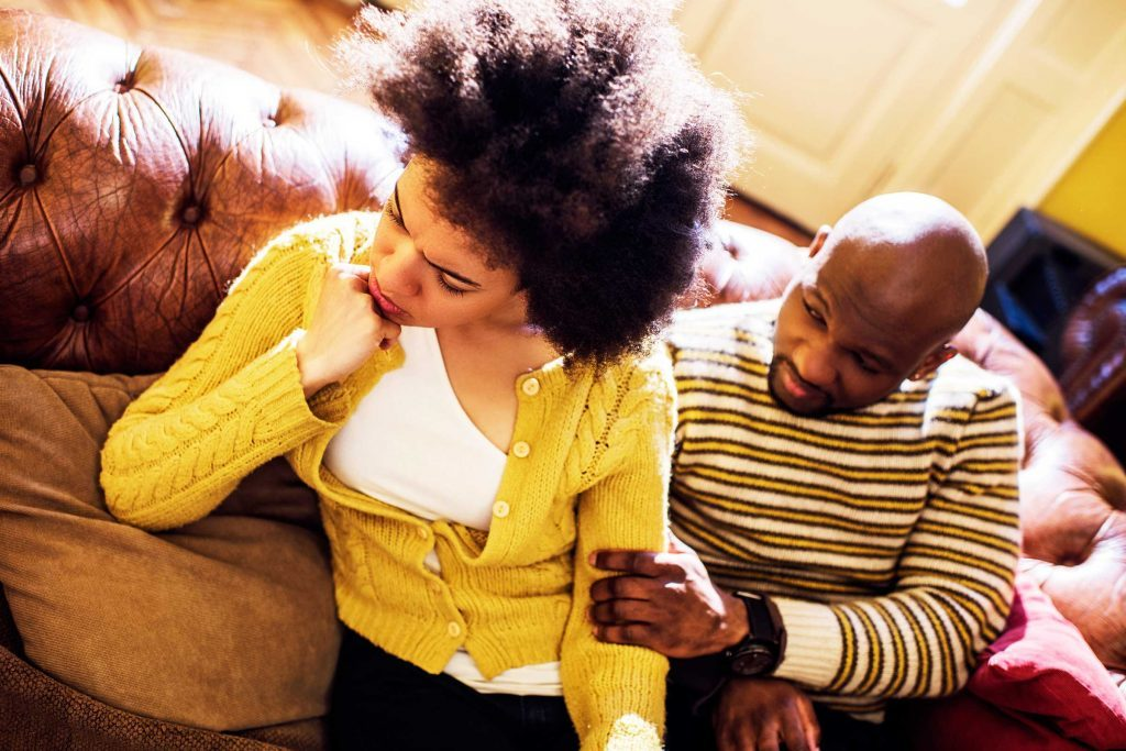 couple on couch, man holding upset woman's arm