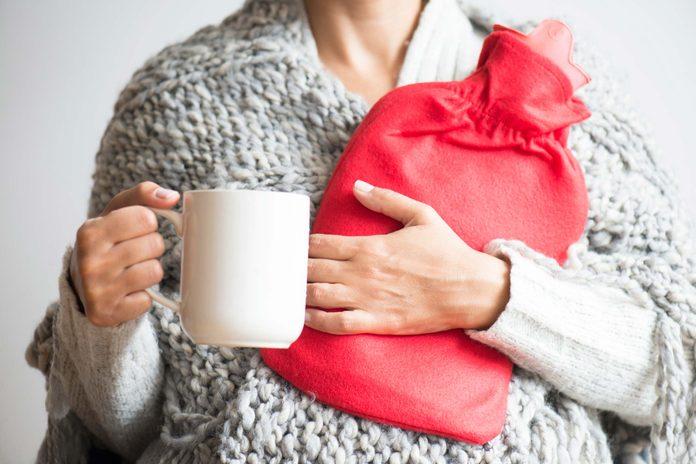 Woman with mug and hot-water bladder