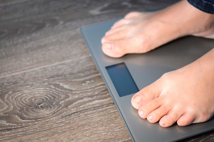 man's feet standing on a scale
