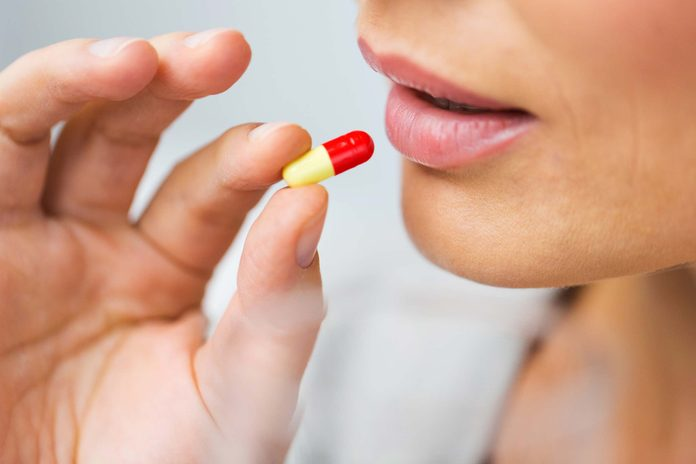closeup of a woman about to take an antibiotic pill