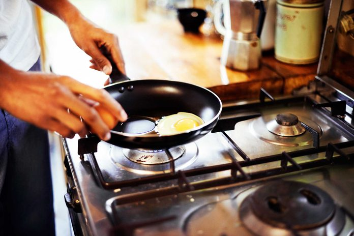 man cooking eggs in a skillet on a stove