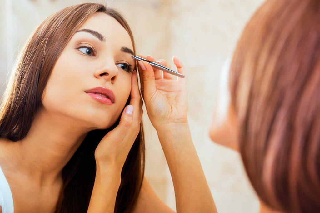 beautiful woman tweezing her eyebrows in the mirror