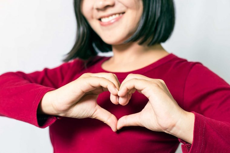 woman using hands to make heart sign