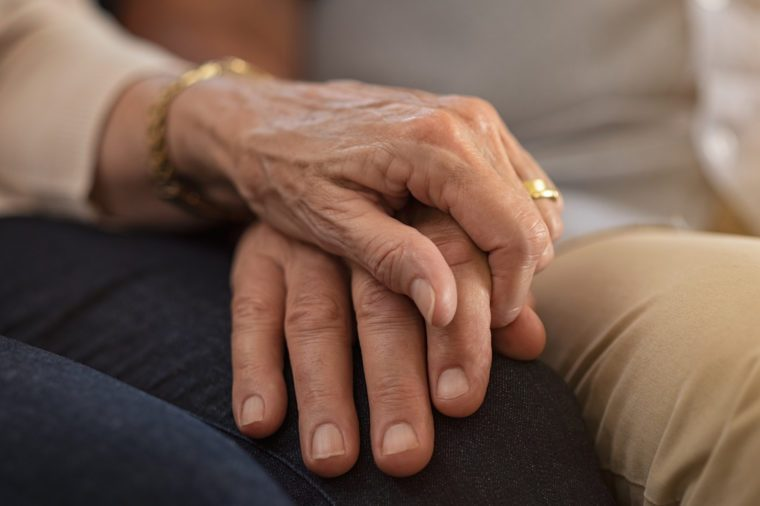 elderly couple holding hands comforting each other