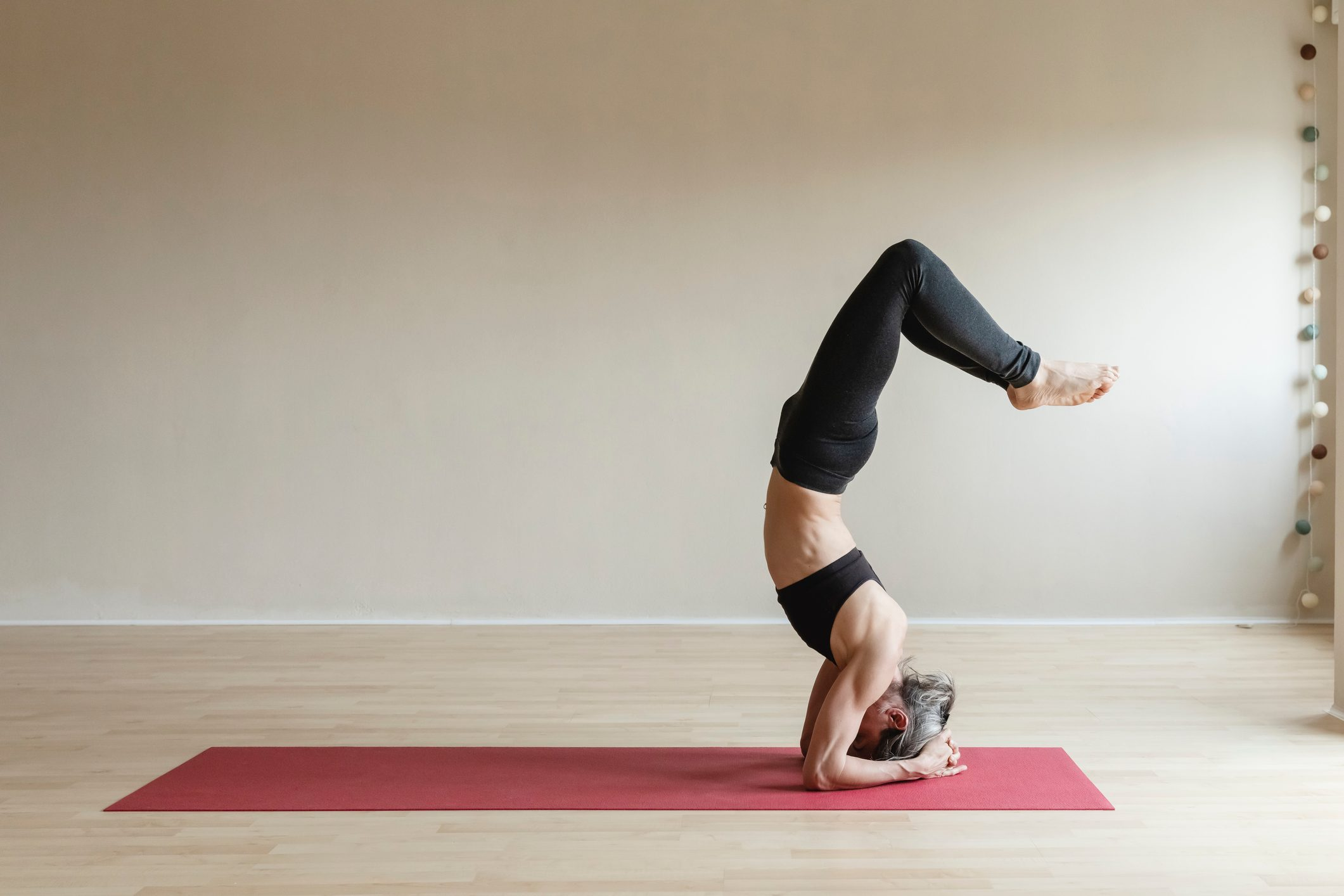 woman doing yoga headstand at home