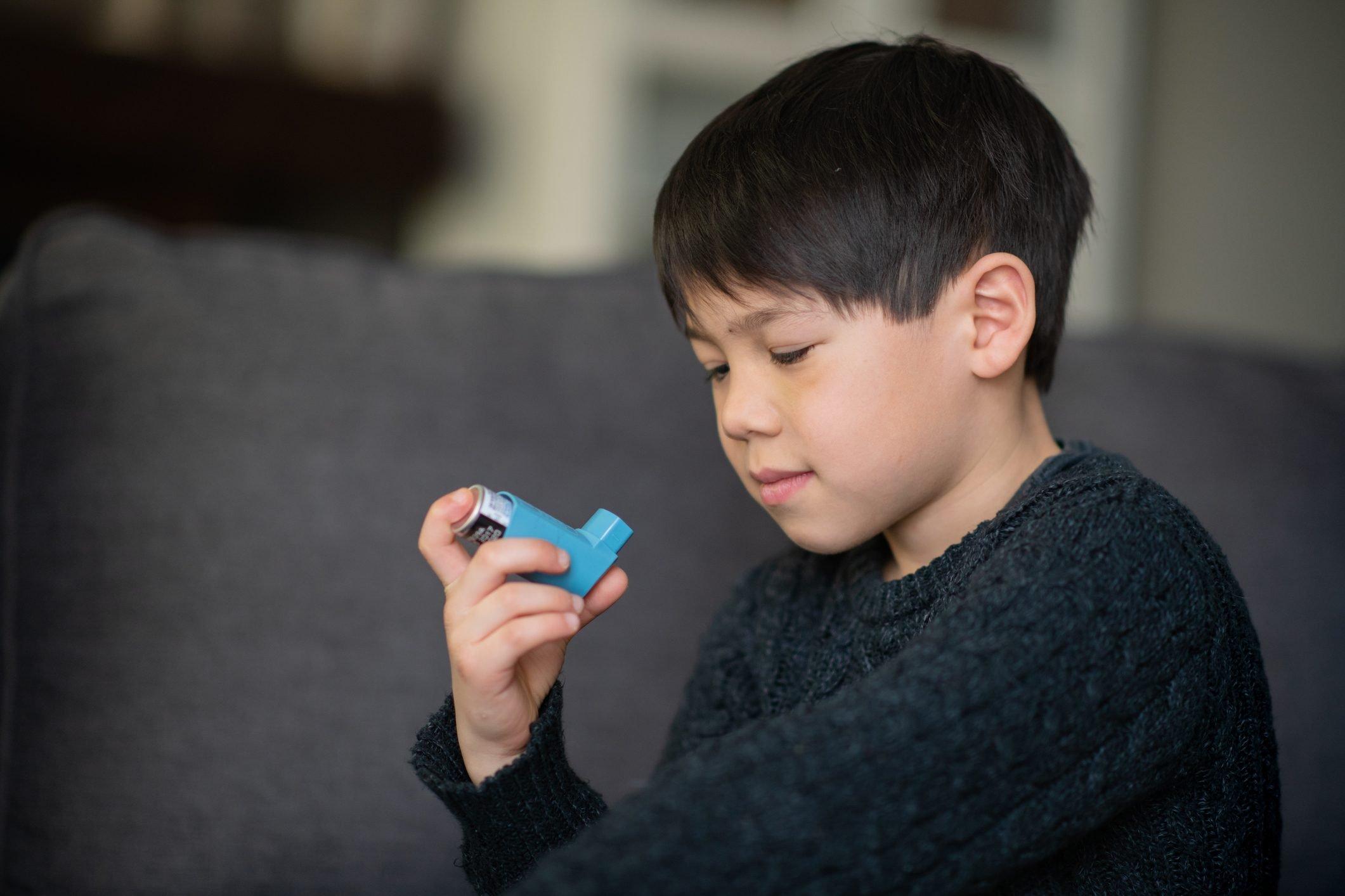 young boy holding a blue inhaler