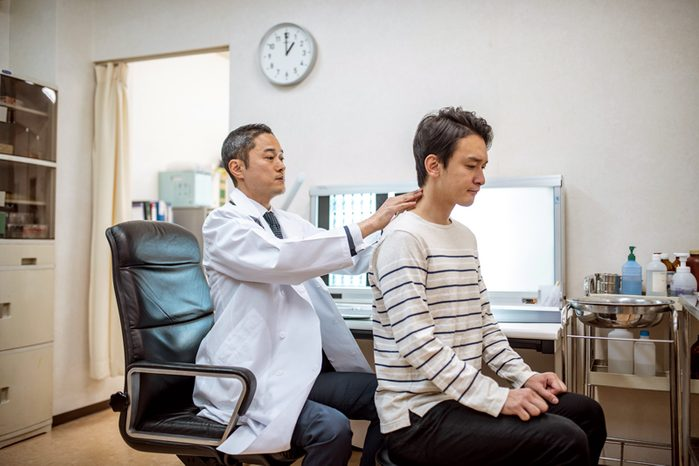chiropractor examining patient's neck and back