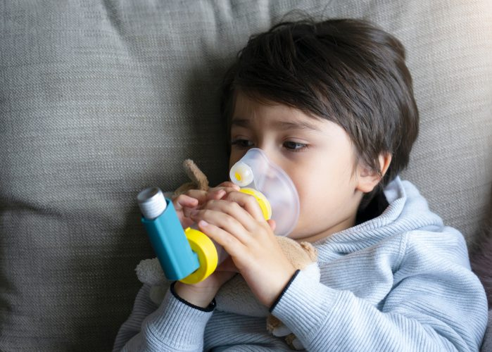 young boy holding medical asthma inhaler while sitting on couch