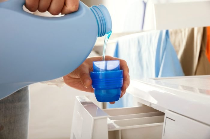 pouring laundry detergent