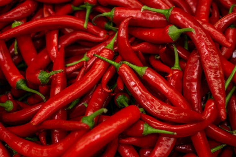 Close up of group of red chili peppers with green stems