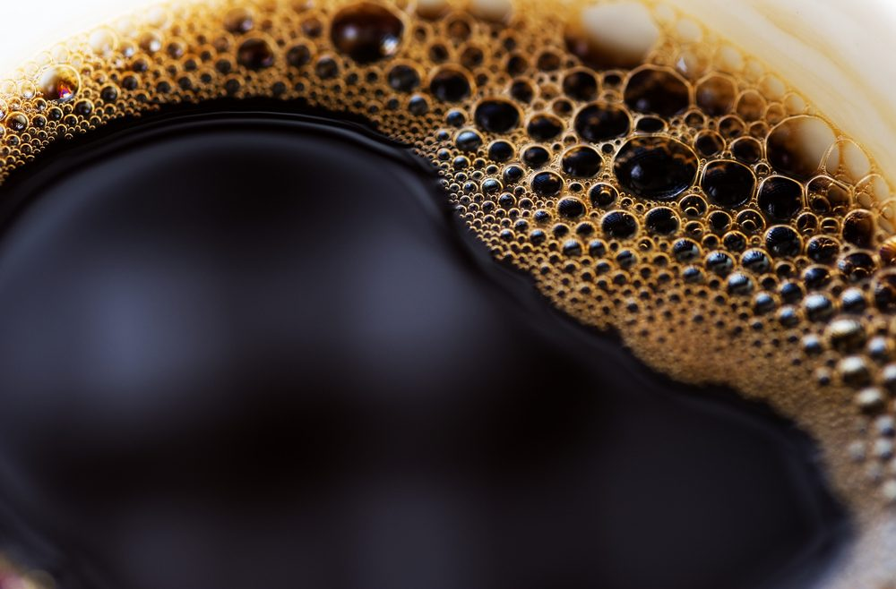 Close up of cup of black coffee with foam on side