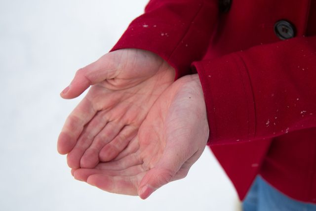 person cupping hands in front of snowy background