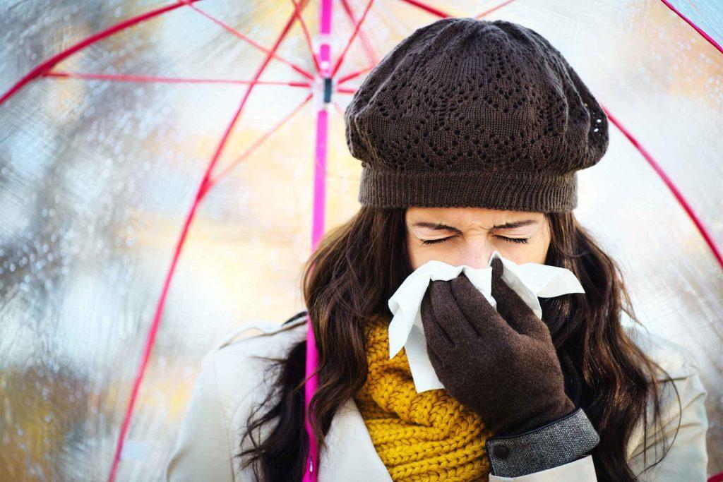 woman bundled up under an umbrella sneezing into a tissue