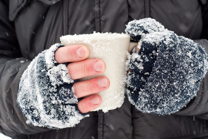 hands with snowy fingerless gloves clutching a mug