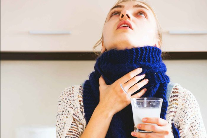 woman with scarf gargling with glass of salt water in hand
