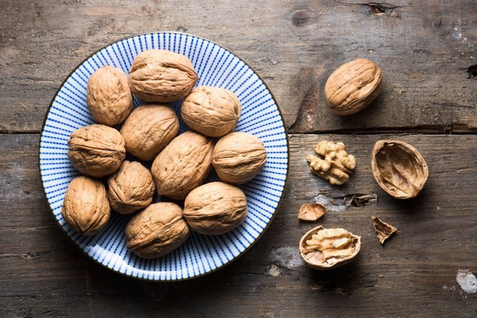 whole and shelled walnuts on a a blue plate