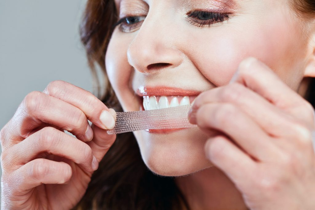 woman applying a teeth-whitening strip