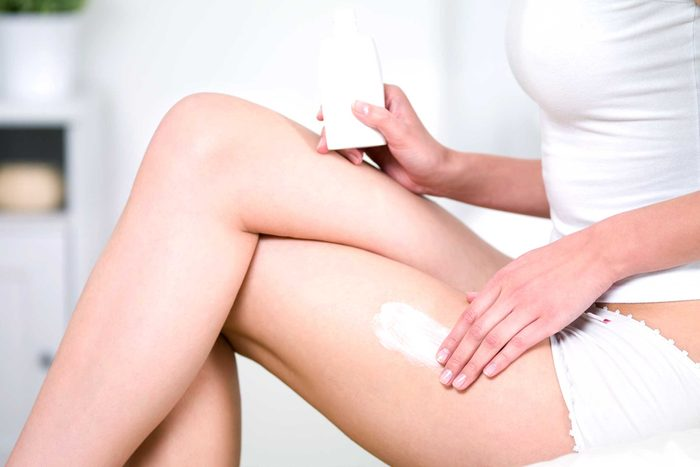 woman rubbing lotion on thigh