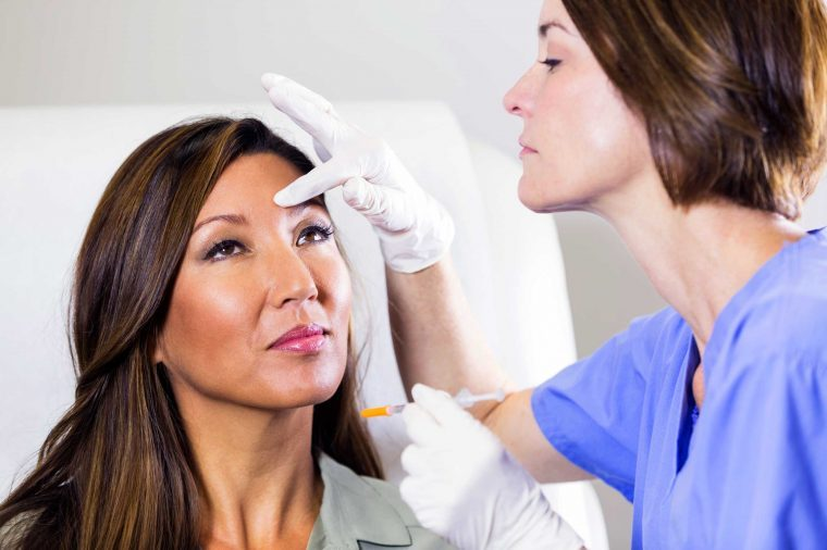 dermatologist with needle and hand on woman's forehead