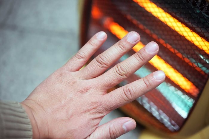Person warming up hands on heater