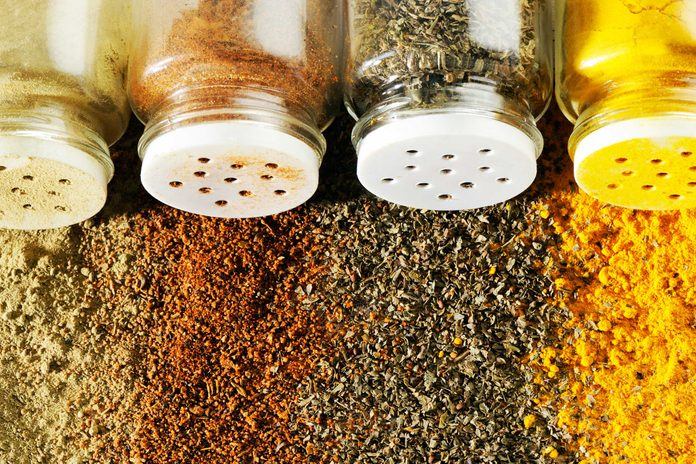 Spice jars spilling colorful spices on table