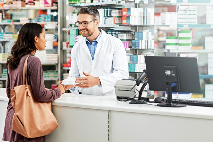 woman getting medicine from a pharmacist