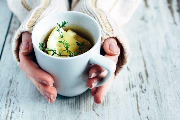 hands clasp big mug of tea
