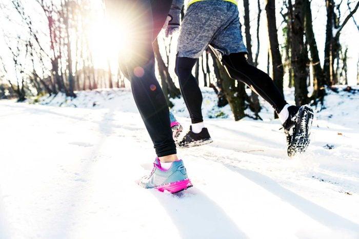 runners' feet in snowy woods