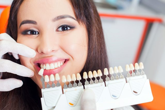 dentist holding up tooth molds next to woman's smile