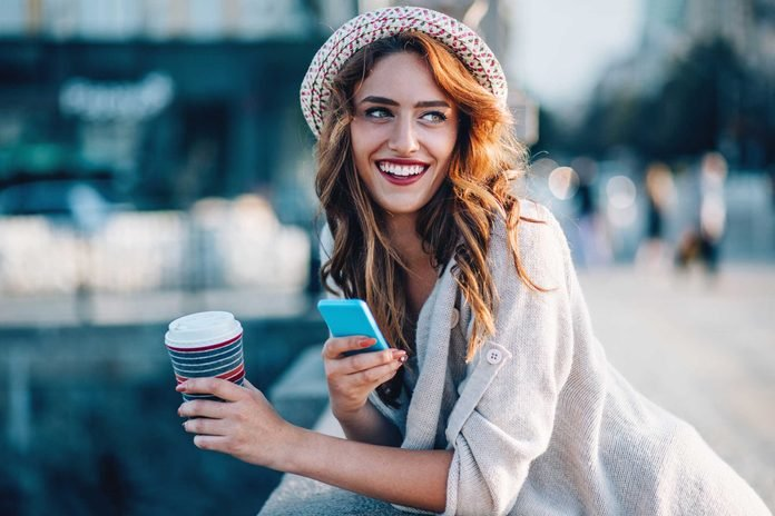 smiling woman with to-go coffee and phone