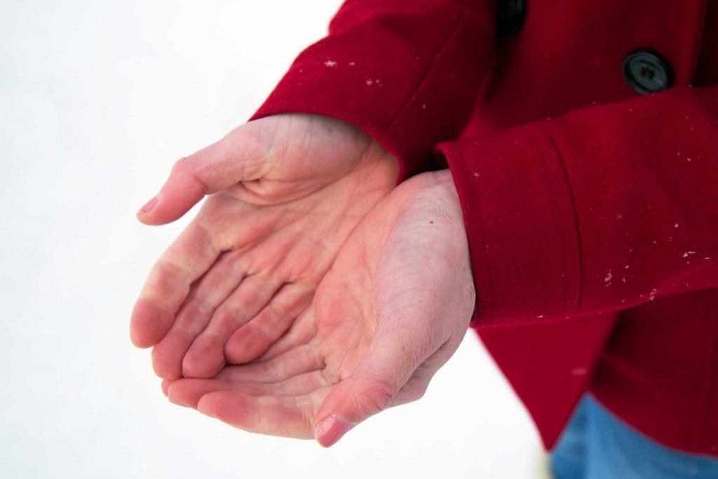 Man cups hands in snow